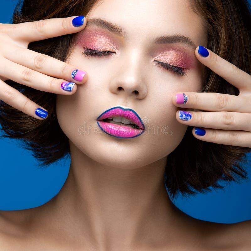 Muchacha modelo hermosa con maquillaje brillante y esmalte de uñas coloreado Cara de la belleza Clavos coloridos cortos fotos de archivo libres de regalías