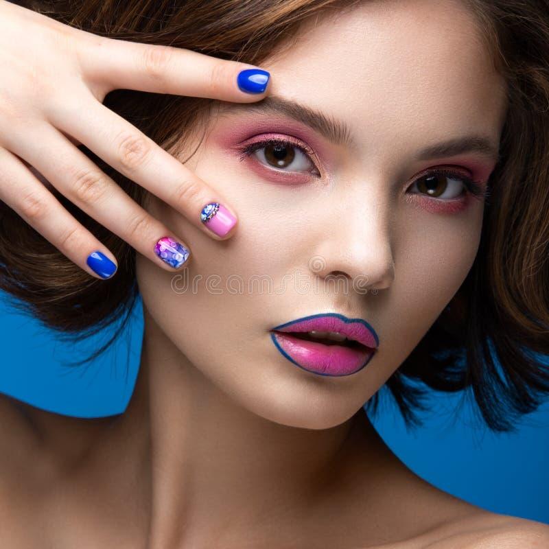 Muchacha modelo hermosa con maquillaje brillante y esmalte de uñas coloreado Cara de la belleza Clavos coloridos cortos foto de archivo libre de regalías