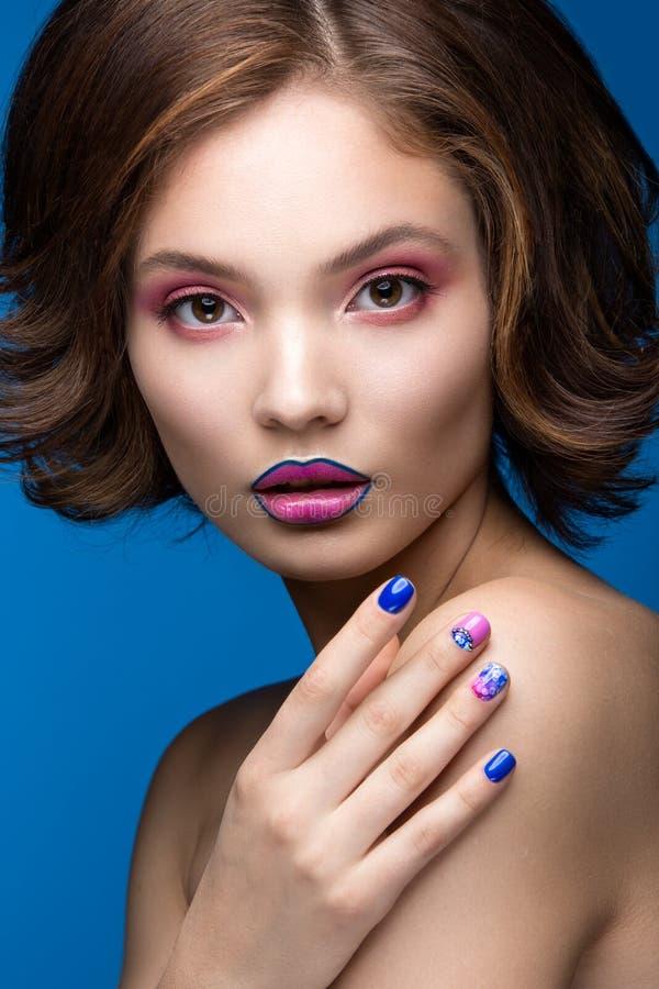 Muchacha modelo hermosa con maquillaje brillante y esmalte de uñas coloreado Cara de la belleza Clavos coloridos cortos foto de archivo