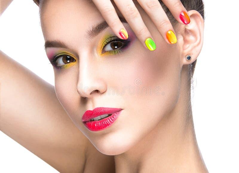 Muchacha modelo hermosa con maquillaje coloreado brillante y esmalte de uñas en la imagen del verano Cara de la belleza Clavos co fotografía de archivo libre de regalías
