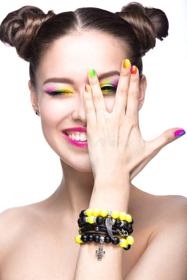 Muchacha modelo hermosa con maquillaje coloreado brillante y esmalte de uñas en la imagen del verano Cara de la belleza Clavos co imagenes de archivo