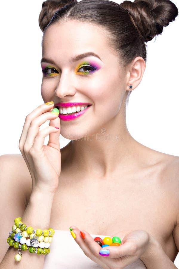 Muchacha modelo hermosa con maquillaje coloreado brillante y esmalte de uñas en la imagen del verano Cara de la belleza Clavos co imagen de archivo