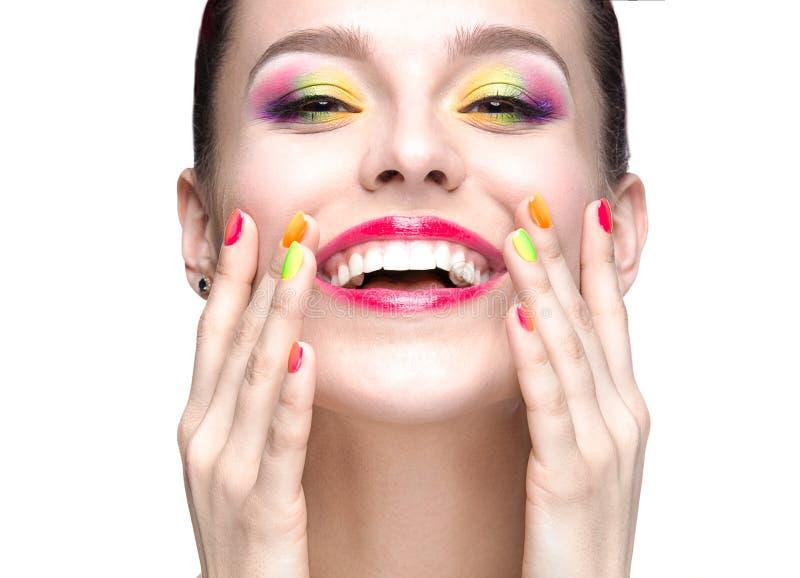 Muchacha modelo hermosa con maquillaje coloreado brillante y esmalte de uñas en la imagen del verano Cara de la belleza Clavos co imagen de archivo libre de regalías