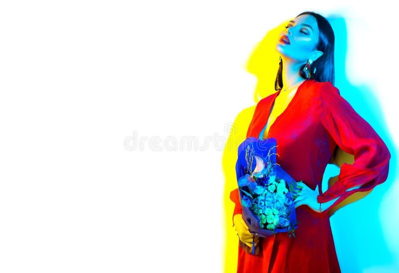 Muchacha modelo morena atractiva con el ramo de flores hermosas en el fondo blanco Mujer joven de la belleza con el manojo de flo fotografía de archivo libre de regalías