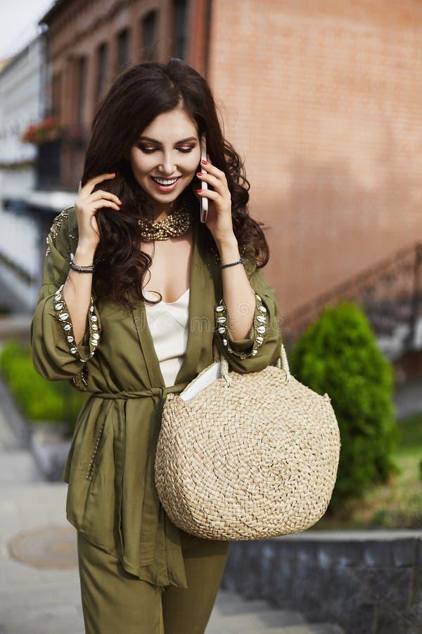 Muchacha modelo morena atractiva y de moda con maquillaje brillante profesional y con la sonrisa brillante en verde elegante fotos de archivo libres de regalías