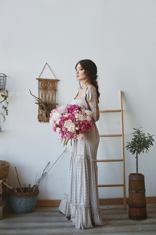 Muchacha modelo morena hermosa con los labios llenos atractivos y con los ojos cerrados en el vestido elegante con un ramo grande imagenes de archivo