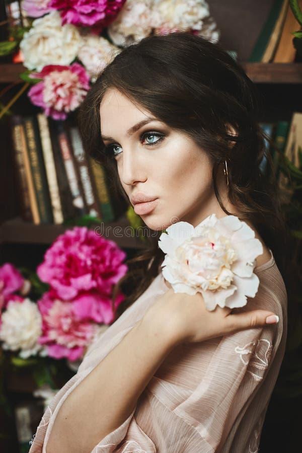 Muchacha modelo morena hermosa y de moda con los ojos azulverdes y con los labios atractivos llenos, en el vestido beige que pres foto de archivo libre de regalías
