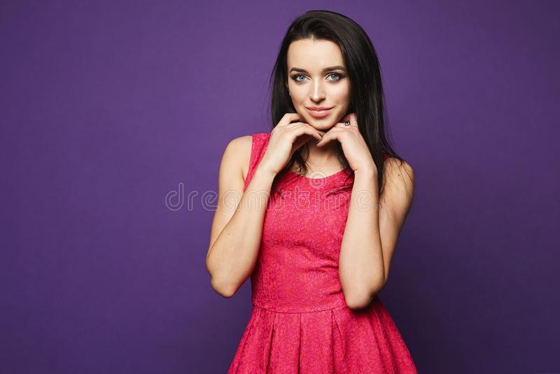 Muchacha modelo morena hermosa y de moda con maquillaje brillante y cuerpo perfecto en la sonrisa rosada elegante corta del vesti imagen de archivo libre de regalías