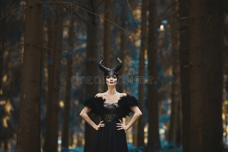 Muchacha modelo morena hermosa y de moda en la imagen de maléfico - historia del cuento de hadas fotos de archivo libres de regalías