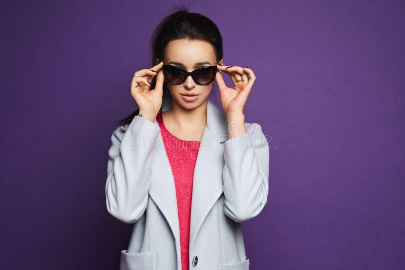 Muchacha modelo morena hermosa y de moda en vestido rojo y la capa que ajustan sus gafas de sol y que presentan en el fondo viole imagenes de archivo