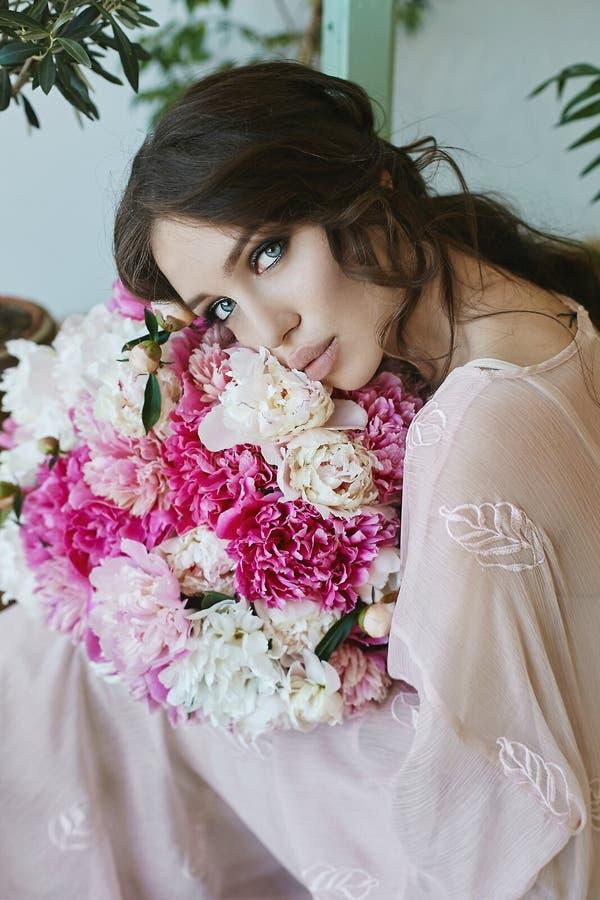 Muchacha modelo morena hermosa y sensual con los labios atractivos grandes y con los ojos azules, en vestido beige con el ramo gr foto de archivo libre de regalías