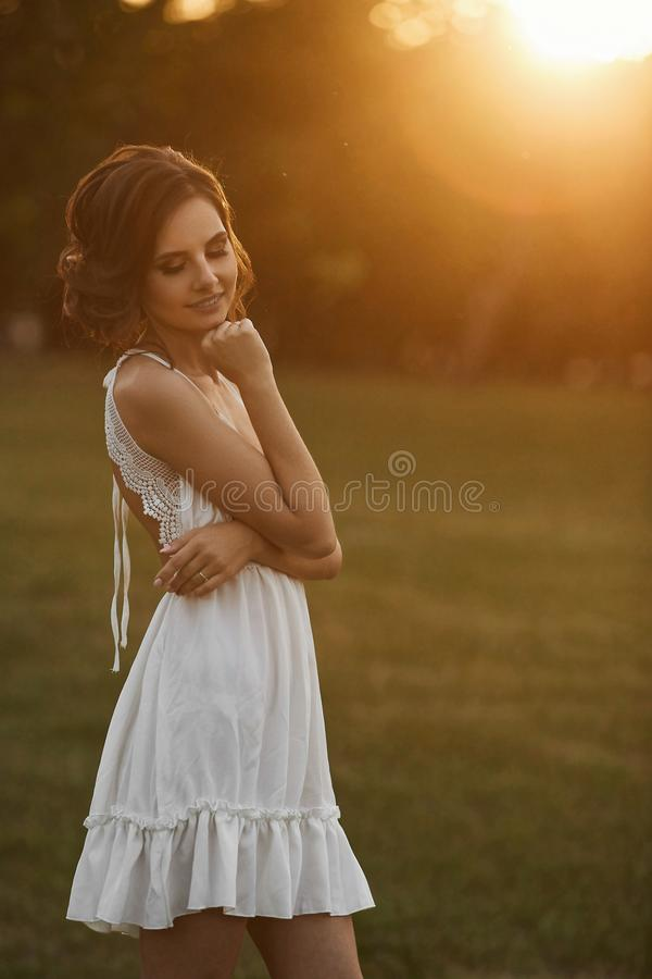 Muchacha modelo morena hermosa y sensual en vestido blanco corto, con los ojos cerrados y el maquillaje apacible, presentando en  fotos de archivo