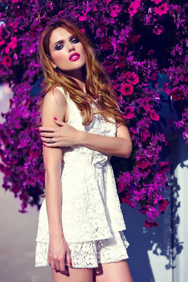 Muchacha modelo rubia de la forma de vida en paño casual cerca de las flores con los labios rosados foto de archivo