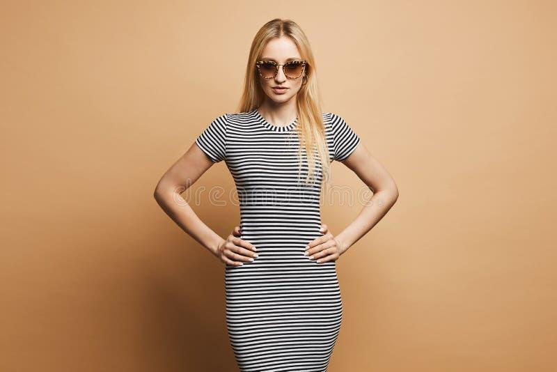 Muchacha modelo rubia de moda y hermosa con el cuerpo delgado y las gafas de sol elegantes del leopardo, en el Dr. rayado blanco  fotografía de archivo libre de regalías
