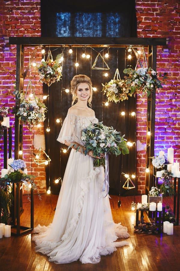 Muchacha modelo rubia feliz y hermosa con el peinado de moda en un vestido elegante beige, con el ramo de lujo grande fotografía de archivo libre de regalías