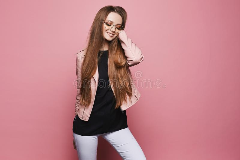 Muchacha modelo rubia hermosa y feliz con maquillaje brillante y con los vidrios de moda en la chaqueta de cuero y en negro foto de archivo