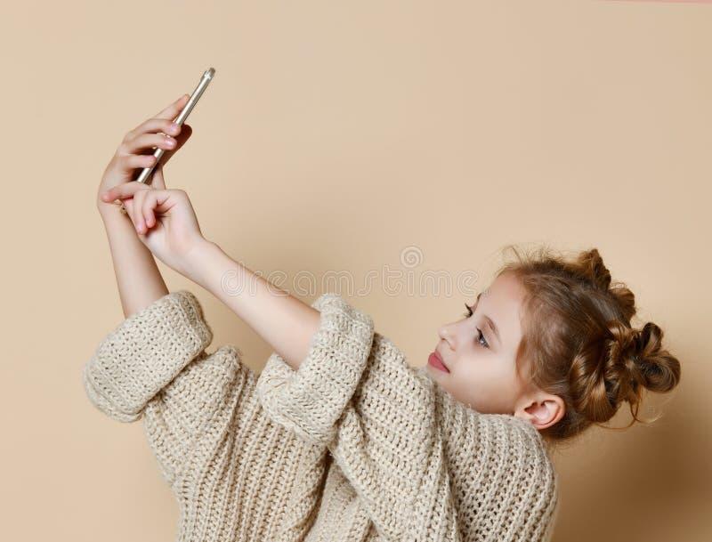 Muchacha moderna bonita en suéter enorme que sonríe y que hace el selfie en smartphone imagen de archivo