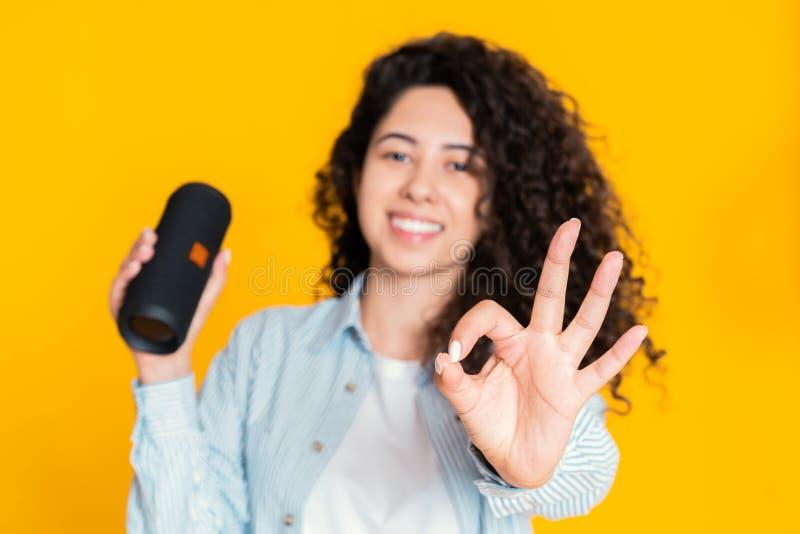Muchacha moderna con la muestra aceptable de la demostración inalámbrica del altavoz portátil Mujer hermosa joven con el peinado  fotos de archivo libres de regalías