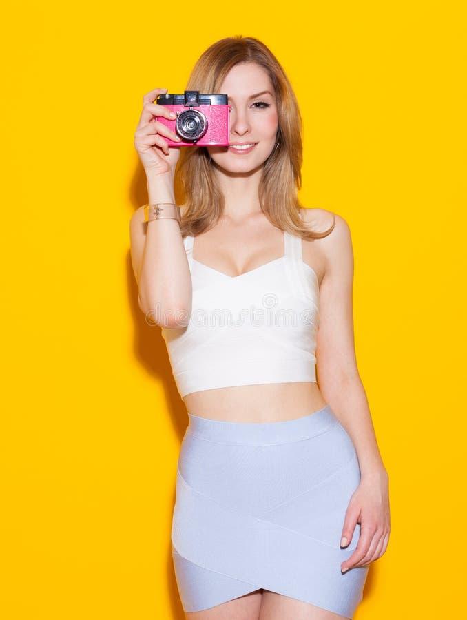 Muchacha moderna de moda que presenta en top y falda coloridos con una cámara del vintage en su mano un fondo amarillo en el estu imágenes de archivo libres de regalías