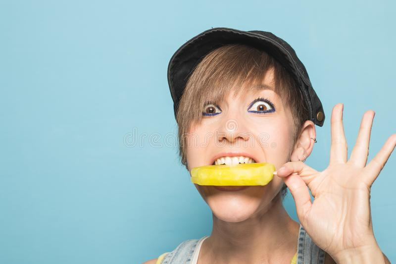 Muchacha moderna que come el helado con la expresión divertida fotografía de archivo