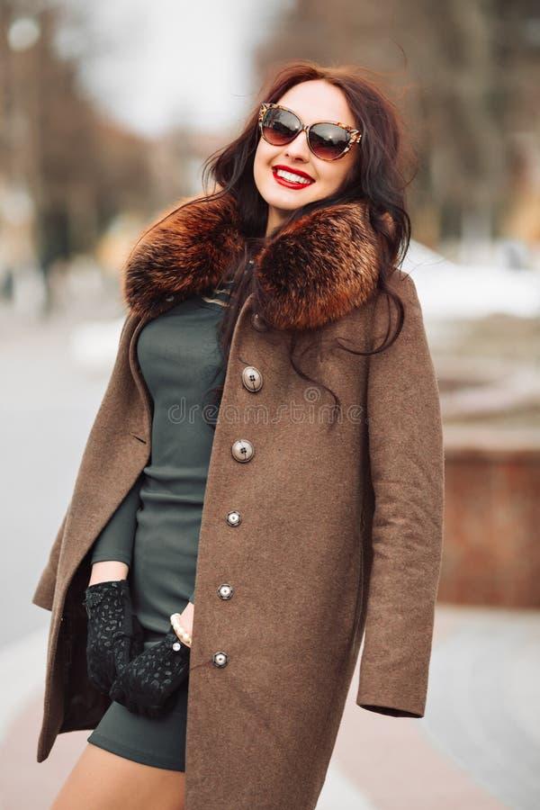 Muchacha morena atractiva atractiva hermosa en un vestido y un abrigo de pieles verdes elegantes con una piel mullida, los guante imagen de archivo