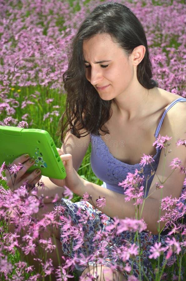 Muchacha morena atractiva hermosa que usa la tableta en prado magnífico foto de archivo