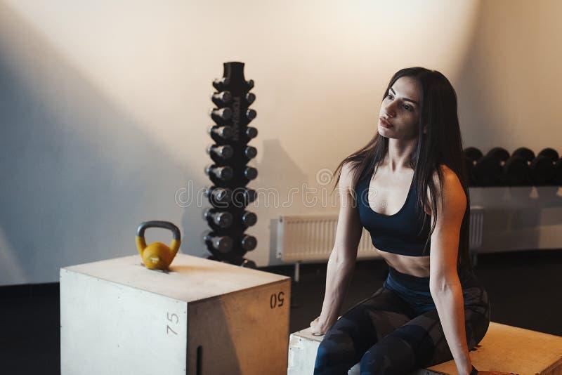 Muchacha morena atractiva joven que se relaja en el gimnasio en la caja de madera para el crossfit después de entrenamiento imagen de archivo