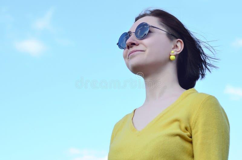 Muchacha morena atractiva y linda en un suéter amarillo contra a imagenes de archivo