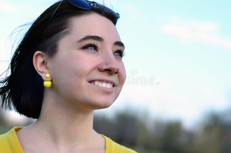 Muchacha morena atractiva y linda en un suéter amarillo contra a imágenes de archivo libres de regalías