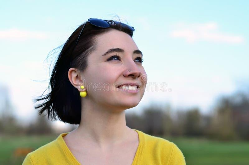 Muchacha morena atractiva y linda en un suéter amarillo contra a imagen de archivo libre de regalías