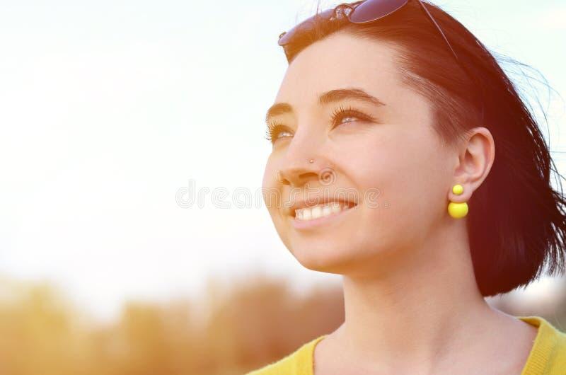 Muchacha morena atractiva y linda en un suéter amarillo contra a imagen de archivo