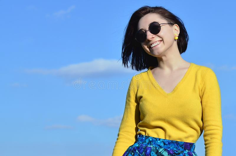 Muchacha morena atractiva y linda en un suéter amarillo contra a foto de archivo