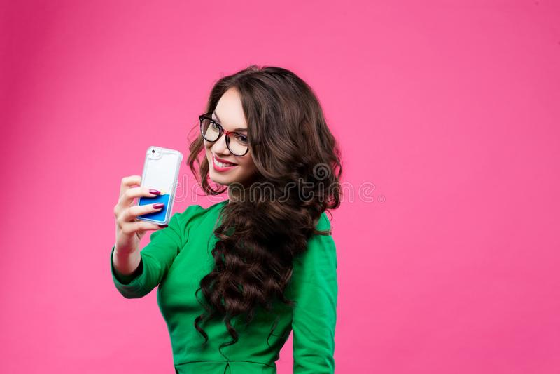Muchacha morena bonita con el pelo ondulado largo que muestra el palillo hacia fuera y que toma el autorretrato en su teléfono el fotografía de archivo