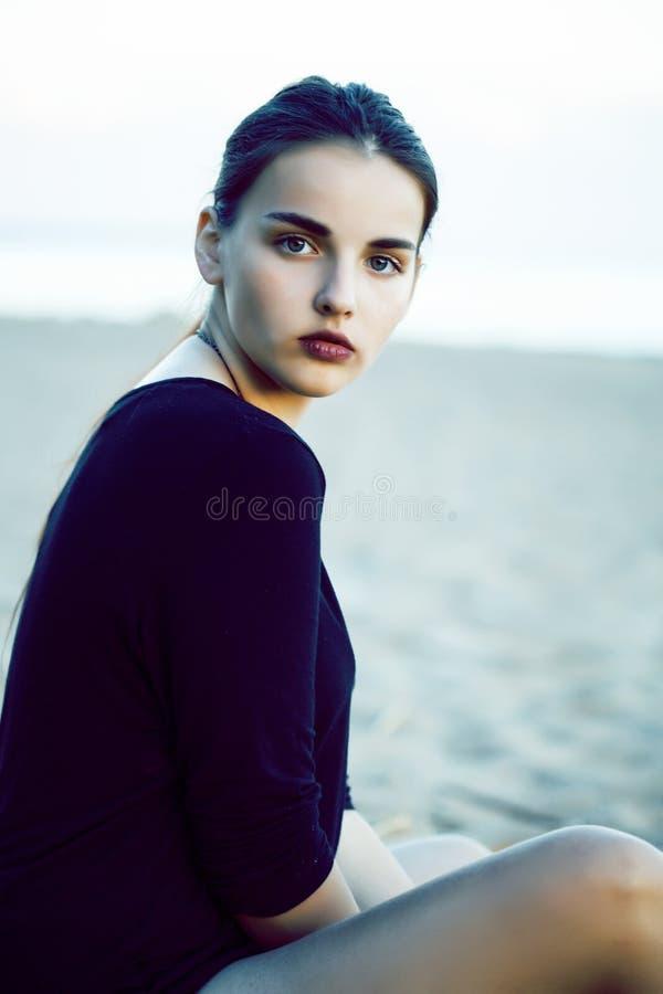 Muchacha morena bonita joven con el pelo largo que espera solamente en la arena en la costa, concepto de la gente de la forma de  foto de archivo