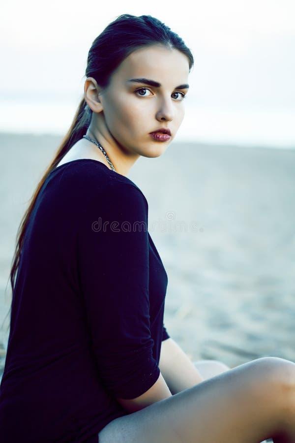 Muchacha morena bonita joven con el pelo largo que espera solamente en la arena en la costa, concepto de la gente de la forma de  fotos de archivo
