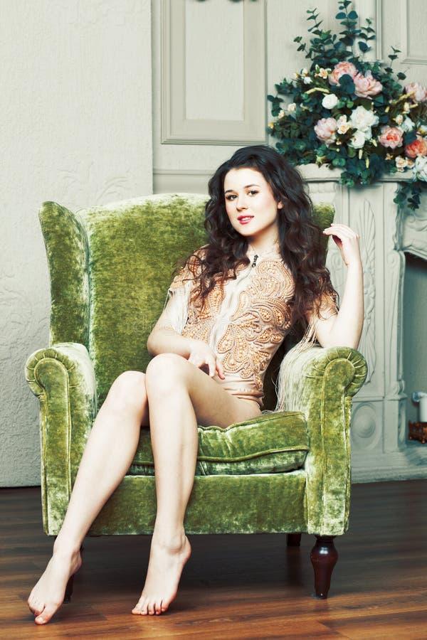 Muchacha morena bonita joven en vestido de la moda en el sofá que presenta en el lu imagenes de archivo