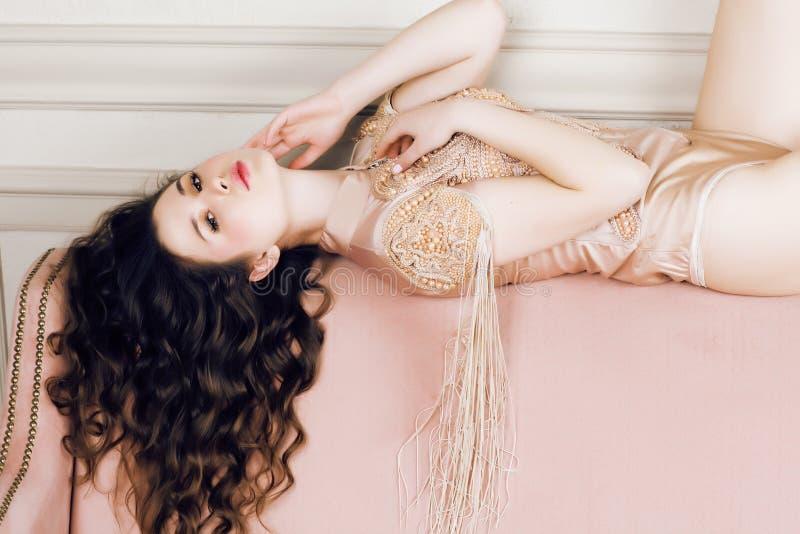 Muchacha morena bonita joven en vestido de la moda en el sofá que presenta en el interior casero rico de lujo, concepto moderno d foto de archivo