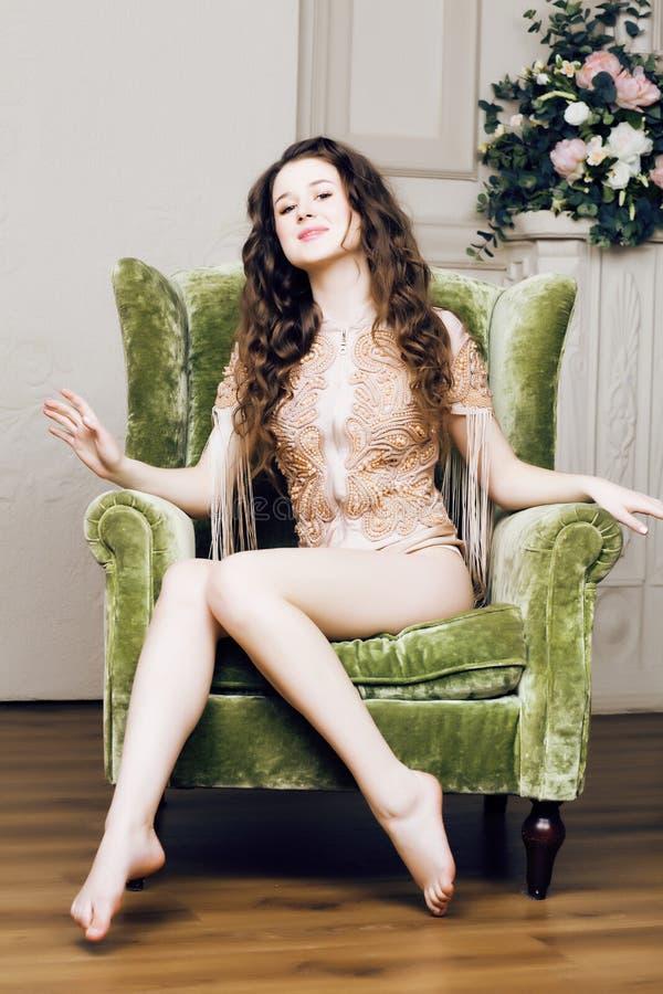Muchacha morena bonita joven en vestido de la moda en el sofá que presenta en el interior casero rico de lujo, concepto moderno d imágenes de archivo libres de regalías