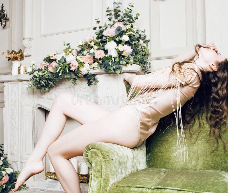 Muchacha morena bonita joven en vestido de la moda en el sofá que presenta en el interior casero rico de lujo, concepto moderno d imagenes de archivo