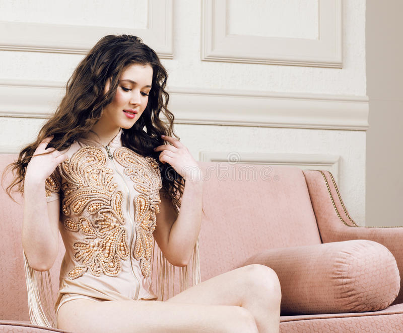 Muchacha morena bonita joven en vestido de la moda en el sofá que presenta en el interior casero rico de lujo, concepto moderno d imagen de archivo libre de regalías