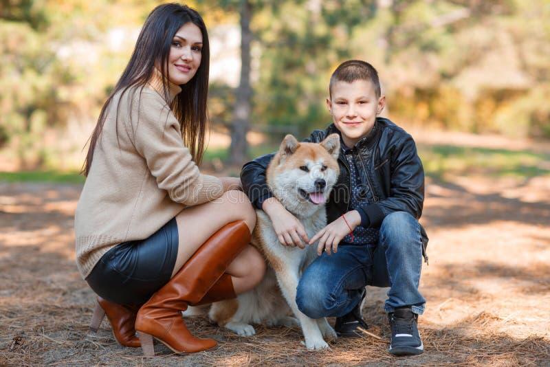 Muchacha morena bonita y un niño pequeño que camina con el perro en el parque Concepto animal imagen de archivo libre de regalías