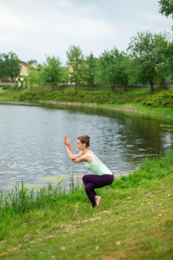 Muchacha morena caucásica hermosa joven que hace yoga en un césped verde contra la perspectiva del río Eagle Pose, Garudasana fotografía de archivo