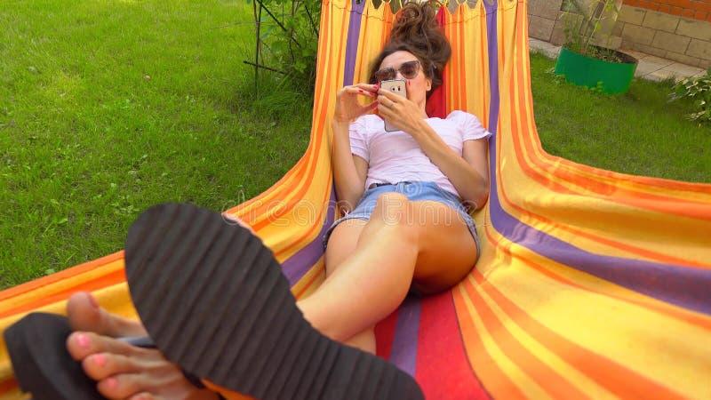 Muchacha morena caucásica hermosa que balancea en hamaca brillante y que usa su smartphone fotografía de archivo