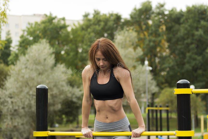 Muchacha morena caucásica inclinada en barras de deportes La mujer joven de la aptitud atractiva en al aire libre resuelve el gim foto de archivo