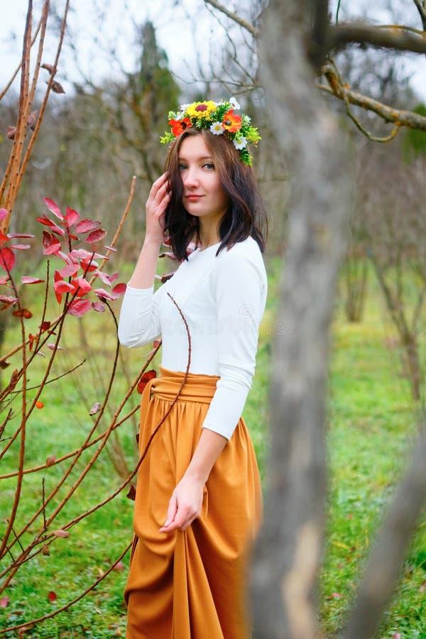 Muchacha morena con la guirnalda de la flor en el parque colorido del otoño imagen de archivo