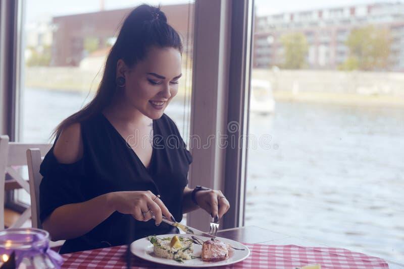 Muchacha morena con una cola que se sienta en un restaurante en la nave en el fondo del río La muchacha intenta de color salmón c fotos de archivo