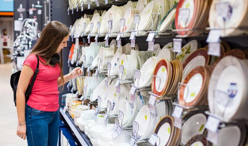 Muchacha morena del adolescente en la camiseta coralina con el pelo largo que elige una placa de los platos en tienda del superme foto de archivo libre de regalías