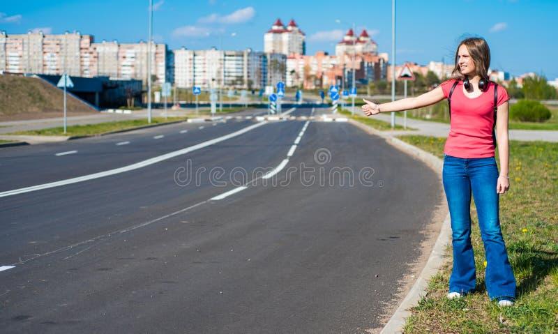 Muchacha morena del adolescente en la camiseta coralina con el pelo largo que hace autostop por el borde de la carretera Manosear fotografía de archivo