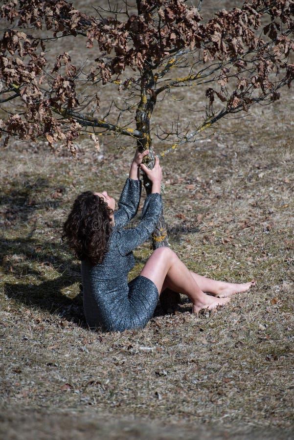 Muchacha morena del pelo ondulado en las montañas, jugando la sentada en la hierba que sacude un árbol joven fotos de archivo libres de regalías