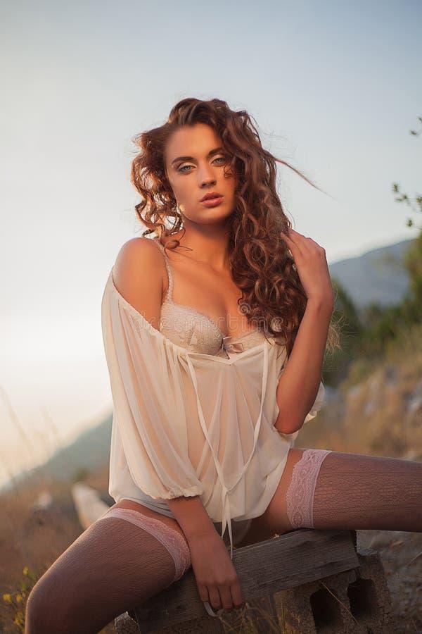 Muchacha morena del retrato atractivo con el pelo rizado imagenes de archivo